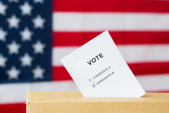 Vote inserted into ballot box slot on election. Voting and civil rights concept - vote with two candidates inserted into ballot box slot on election over Royalty Free Stock Images