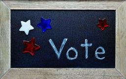 Vote la escritura, rodeada por las estrellas rojas, blancas y azules Imágenes de archivo libres de regalías