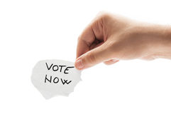 Vote Now. Concept using a hand holding a piece of paper and the text written by hand with a permanent marker Stock Photography