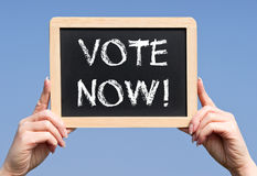 Vote Now - female hands holding chalkboard with text. Blue sky in the background royalty free stock image