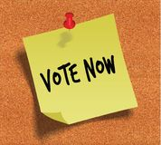 VOTE NOW handwritten on yellow sticky paper note over cork noticeboard background. Royalty Free Stock Photography