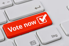 Vote now. A keyboard with a red button - Vote now royalty free stock photo