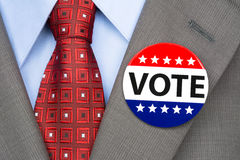 Vote pin on brown suit. A voter wears a vote pin on his suit lapel during election season Royalty Free Stock Photography