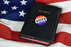 Vote pin on Holy Bible. Vote button and Holy Bible on American flag royalty free stock photography