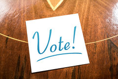 Vote Reminder On Paper Lying On Wooden Cupboard Stock Image