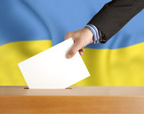 Vote Ukraine. Male hand with ballot and box on Flag of Ukraine Royalty Free Stock Photography