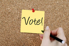 VOTE. Woman hand writing VOTE on yellow adhesive note pinned on cork noticeboard Stock Image