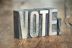 Vote word wood. Vote exclamation made from wooden letterpress type on grunge wood Stock Photo