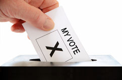 Voter. A hand placing a voting slip into a ballot box against a white background Royalty Free Stock Photography