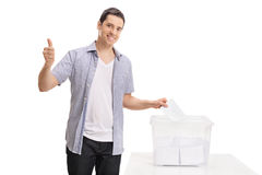 Voter casting vote into ballot box and making thumb up Royalty Free Stock Photography