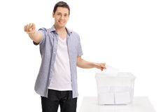 Voter casting vote into ballot box and pointing at camera Stock Photo