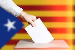 Voter Holds Envelope In Hand Above Vote Ballot. National Catalonia Flag background. Democracy Concept Royalty Free Stock Photos