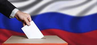 Voter Holds Envelope In Hand Above Vote Ballot On Russia Flag Background. Freedom Democracy Concept. Voter hand puts the ballot into the ballot box. The concept stock image