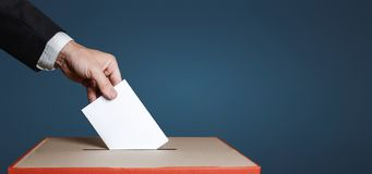 Voter Holds Envelope In Hand Above Vote Ballot On Blue Background. Freedom Democracy Concept. Voter hand puts the ballot into the ballot box. The concept of Royalty Free Stock Images