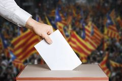 Voter Holds Envelope In Hand Above Vote Ballot. Catalonia Flags background. Democracy Concept. Voter hand puts the ballot into the ballot box. The concept of Stock Photography
