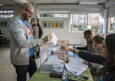 Voter introducing envelope inside urn at electoral college for Spanish general elections in Madrid, Spain Stock Images
