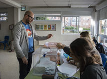 Voter introducing envelope inside urn at electoral college for Spanish general elections in Madrid, Spain Stock Photography