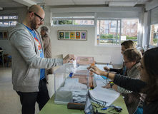 Voter introducing envelope inside urn at electoral college for Spanish general elections in Madrid, Spain Stock Photo