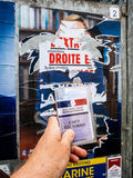 Voter for Marine le Pen holding Carte Electorale in front of the. PARIS, FRANCE - MAY 9, 2017: Carte Electorale in front of Marine Le Pen portrait poster detail royalty free stock photos