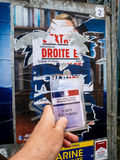 Voter for Marine le Pen holding Carte Electorale in front of the. PARIS, FRANCE - MAY 9, 2017: Carte Electorale in front of Marine Le Pen portrait poster detail stock photography