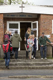 Voters arriving and leaving a Polling Station. Voters at the Polling Station within St Pauls Church Hall in Kings Worthy Winchester Hampshire England UK. Coming Stock Photography