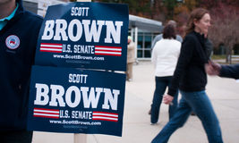 Voters pass a Scott Brown campaign volunteer in New Hampshire. Voters pass a campaign volunteer holding Scott Brown for U.S. Senate campaign signs in Amherst Royalty Free Stock Photography