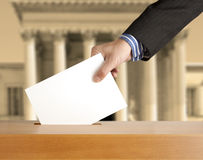 Voting ballot. Hand putting a voting ballot in a slot of box Stock Photos