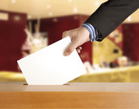 Voting ballot. Hand putting a voting ballot in a slot of box Stock Photo