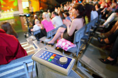 Voting device lies on knee in auditorium Royalty Free Stock Photos
