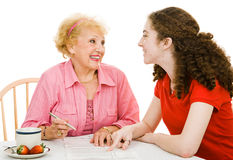 Voting - Discussing Democracy. Senior grandmother and teen grandmother discussing democracy together and filling out absentee ballot. Isolated on white stock photography