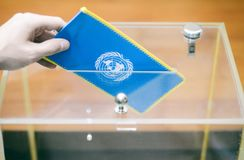 Voting , elections in United Nations. Man inserting Flag of United Nations into ballot box, voting and elections in United Nations stock images