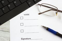 The voting form on the office table near the keyboard, pen and glasses Royalty Free Stock Photos