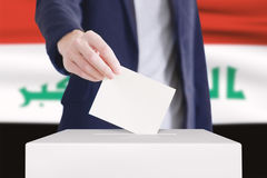 Voting. Man putting a ballot into a voting box with Iraq flag on background royalty free stock images