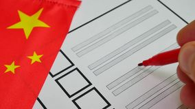 Voting paper ballot in China. Voting in paper ballot by red pencil in China wirh Chinese flag stock footage