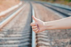 Voting on railway road. Close up female hand with hitch-hiking gesture. stock photos
