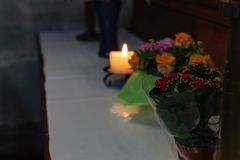 votive altar in church with green and pink flowers stock photo