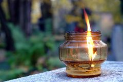 Votive candle. Glass votive candle lit on tombstone royalty free stock photo