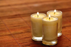 Votive Candle Burning on Bamboo Mat royalty free stock image