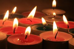 Votive candles. A group of burning votive candles in different colors stock images