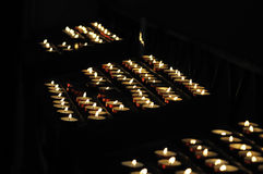 Votive candles. Lit in a pricket stand for praying in a catholic basilica Stock Images