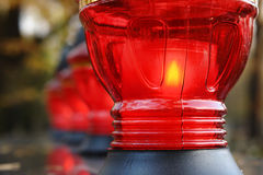 Votive candles. Closeup of red votive candles lit on tombstone royalty free stock image