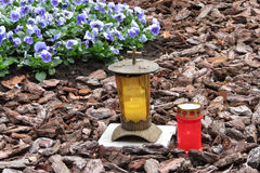 Votive Candles. Burning votive candles on a grave with bark mulch and flowers stock images