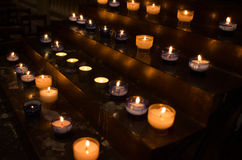 Votive candles. Rows of lit votive candles glow in a dark church Stock Images