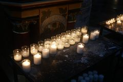 Votive candles in church. Votive candles burning in church royalty free stock photo