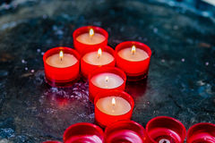 Votive candles forming the Cross. Votive candles form the symbol of the Cross royalty free stock photo