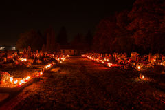Votive candles lantern burning on the graves in Slovak cemetery at night time. All Saints' Day. Solemnity of All Saints Stock Image