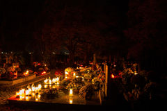Votive candles lantern burning on the graves in Slovak cemetery at night time. All Saints' Day. Solemnity of All Saints Stock Photos