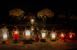 Votive candles lantern burning on the graves in Slovak cemetery at night time. All Saints' Day. Solemnity of All Saints Stock Photo