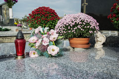 Votive candles lantern and chrysanthemum flowers on tomb stones in graveyard. Graves, tombstones on traditional cemetery. All Saints' Day. All Souls' Day Royalty Free Stock Image