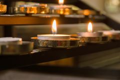 Votive Candles. Lit as prayers for loved ones inside a Christian church royalty free stock photos